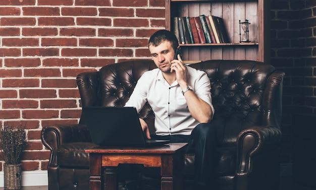 Un homme d'affaires est assis sur le canapé et appelle depuis le téléphone. l'homme riche est entouré d'un intérieur élégant de la pièce