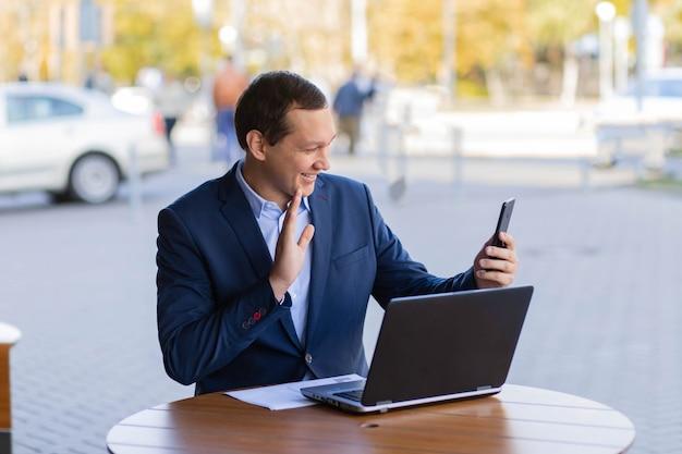Un homme d'affaires est assis à une table dans un café de la rue, agitant sa main lors d'un appel vidéo sur son téléphone portable pendant une pause de travail