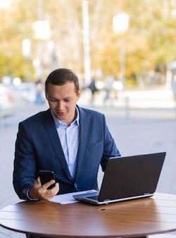 Un homme d'affaires est assis à une table dans un café de la rue et parle d'un appel vidéo sur son téléphone mobile pendant une pause de travail