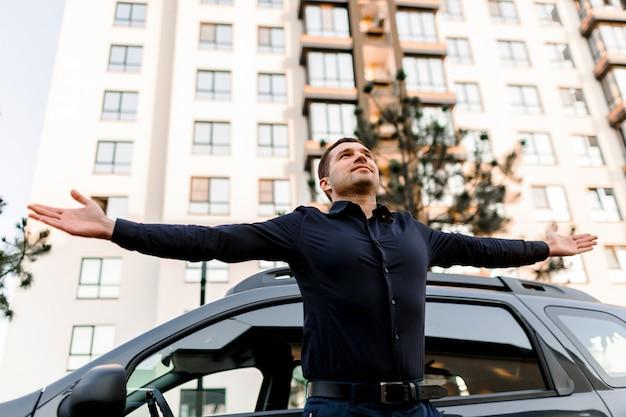 Un homme d'affaires est debout avec les bras tendus. l'homme se sent réussi. c'est un gagnant dans la vie. succès et bien-être financier.