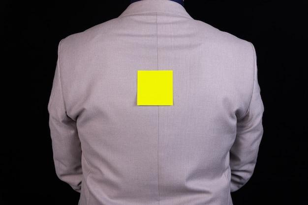 Homme d'affaires est debout avec son dos avec un autocollant