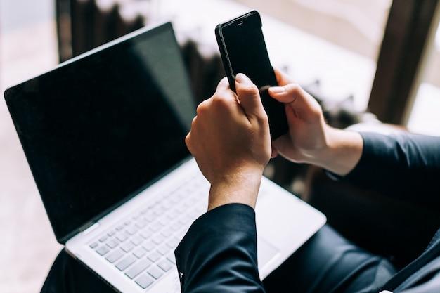 Un homme d'affaires est en train de taper un message dans un smartphone.