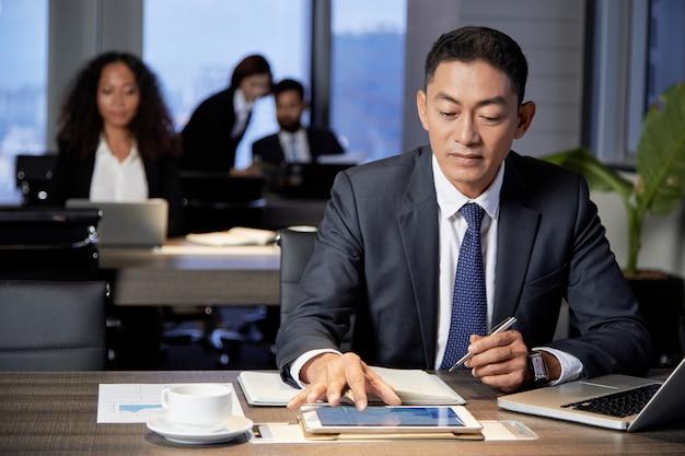 Homme d'affaires ethnique concentré à l'aide de tablette