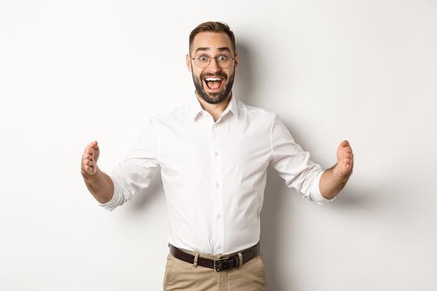 Homme d'affaires étonné montrant un gros objet, décrire quelque chose de grand et l'air excité, debout