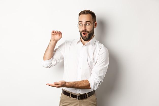 Homme d'affaires étonné montrant un gros objet, décrivez quelque chose de grand et l'air excité, debout sur fond blanc.