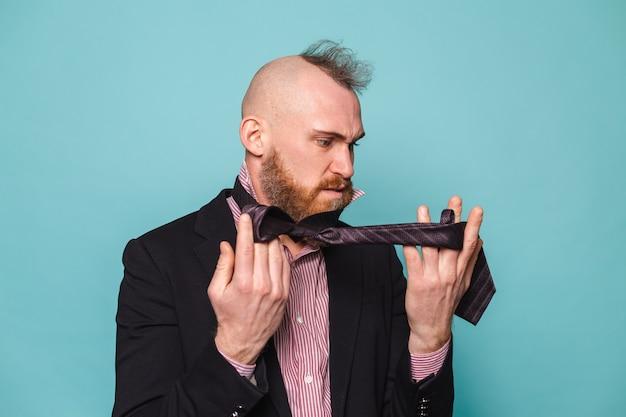 Homme d'affaires européen barbu en costume sombre isolé, en colère en essayant de nouer une cravate ne sais pas comment le faire
