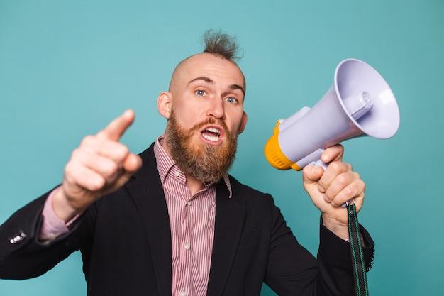 Homme d'affaires européen barbu en costume sombre isolé, avec mégaphone criant avec un visage en colère grave, demandant de l'attention