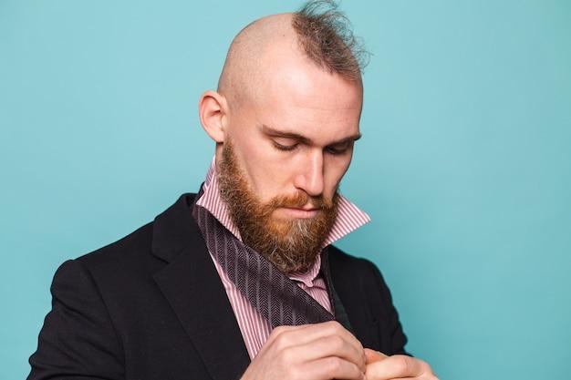 Homme d'affaires européen barbu en costume sombre isolé, noue une cravate