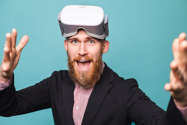 Homme d'affaires européen barbu en costume sombre isolé, portant des lunettes vr sur la tête avec un visage heureux excité
