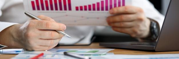 Homme d'affaires examine le rapport financier statistique. réalisation de statistiques commerciales. analyse et comptabilité des méthodes statistiques spécifiques à l'application. rentabilité et fonds de roulement