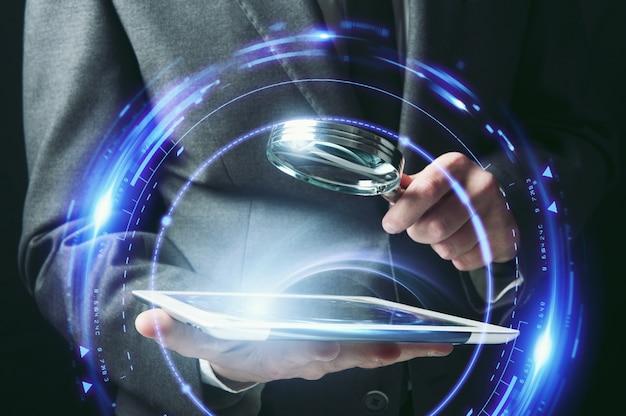 Homme d'affaires examine une tablette avec une loupe.