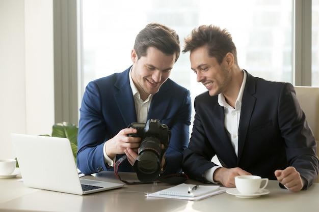 Homme d'affaires excité tenant une caméra professionnelle, montrant photogr