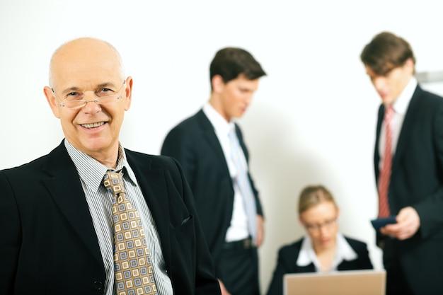 Homme d'affaires expérimenté avec des collègues flous