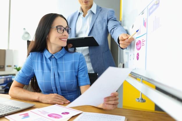 Homme d'affaires expliquant les informations à la femme sur le tableau noir avec des graphiques et des diagrammes