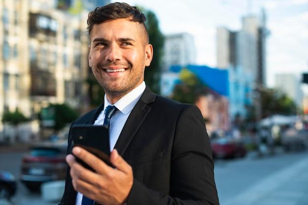 Homme d'affaires à l'extérieur souriant et marchant