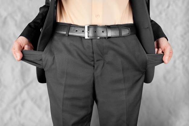 Homme d'affaires en faillite montrant des poches vides avec les mains