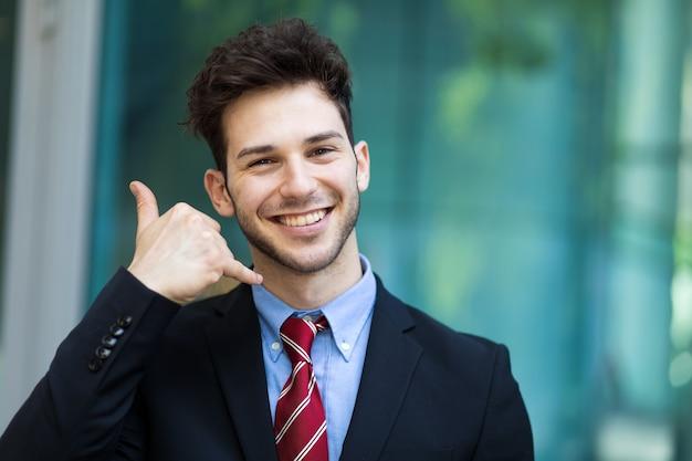 Homme d'affaires faisant un appel moi signe et souriant