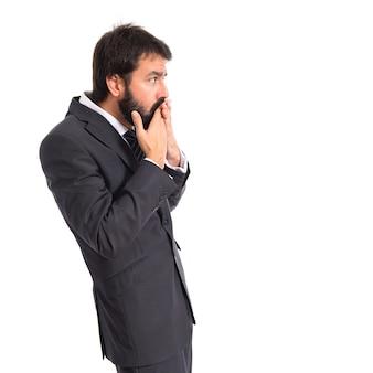 Homme d'affaires faisant un geste de surprise sur fond blanc