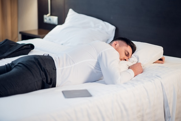 Homme d'affaires fatigué au repos dans une chambre d'hôtel