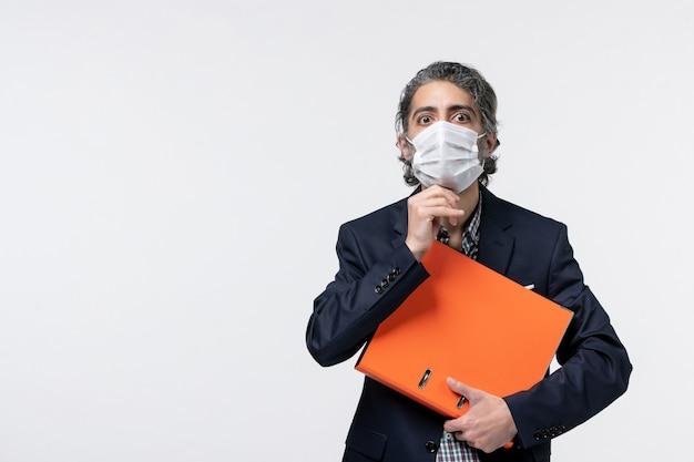 Un homme d'affaires fatigué en costume et tenant ses documents sur une surface blanche