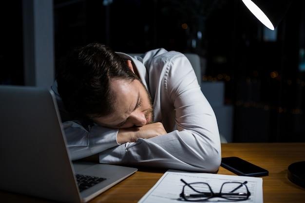 Homme d'affaires fatigué, dormant sur le bureau