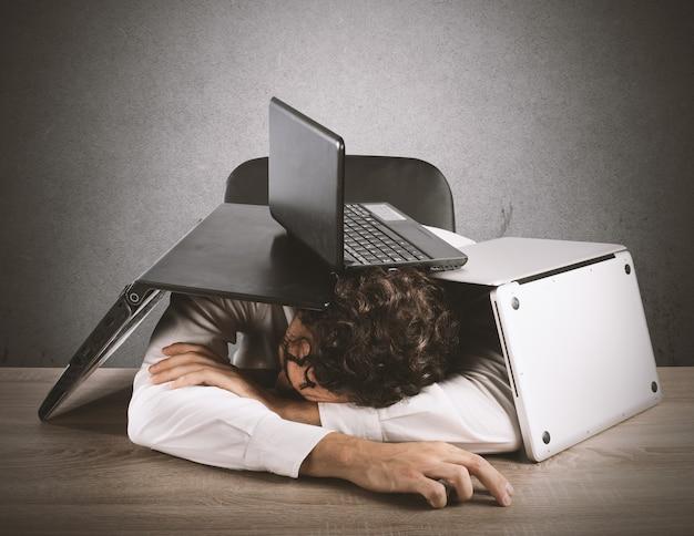 Homme d'affaires fatigué dormant sous une pile d'ordinateurs