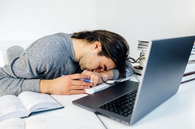 Homme d'affaires fatigué dormant tout en calculant les dépenses au bureau au bureau. un jeune employé de race blanche fait une sieste au bureau sur une table avec une tablette et un ordinateur portable.