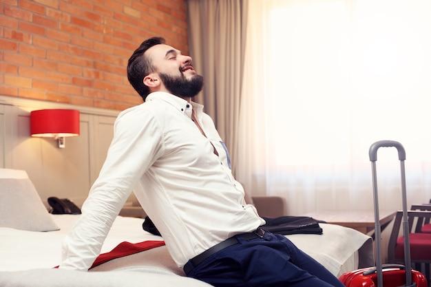 Homme d'affaires fatigué se reposant dans la chambre d'hôtel