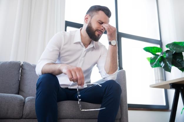 Homme d'affaires fatigué avec stress a mal à la tête et assis sur le canapé avec une douleur sur le visage