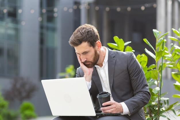 Homme d'affaires fatigué travaillant dans un lieu public sur un banc d'ordinateur portable, bouleversé par la dépression pas satisfait du résultat de son travail