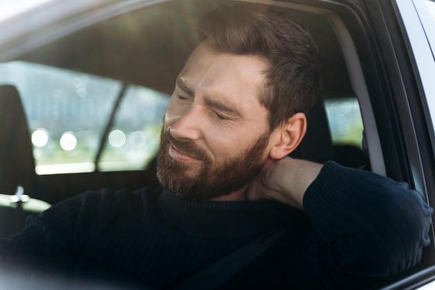 Homme d'affaires fatigué en voiture ressentant une forte douleur au cou et une inflammation des nerfs, après une longue route. concept de problèmes de transport et de santé