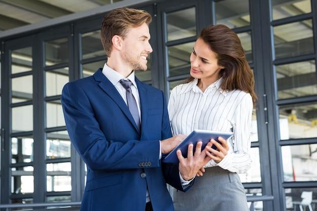 Homme d'affaires et femme d'affaires à l'aide de tablette numérique au bureau