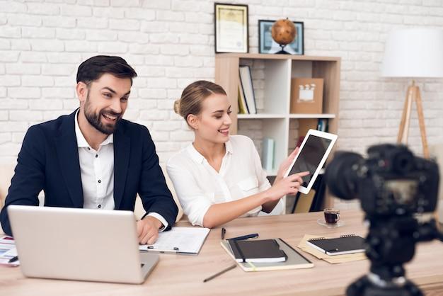 Homme d'affaires et femme d'affaires en blouse montrant sur tablette