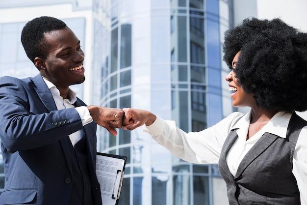 Homme affaires, femme affaires, cogner poing, devant, bâtiment entreprise