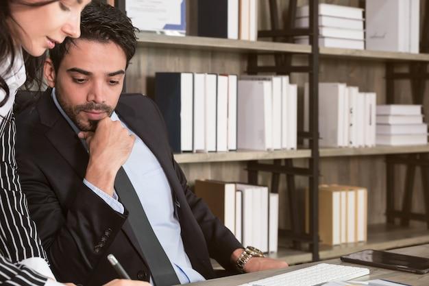 Homme d'affaires et femme d'affaires discutant de documents au bureau