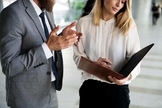 Un homme d'affaires et une femme d'affaires discutant des ordres du jour et regardant le cahier