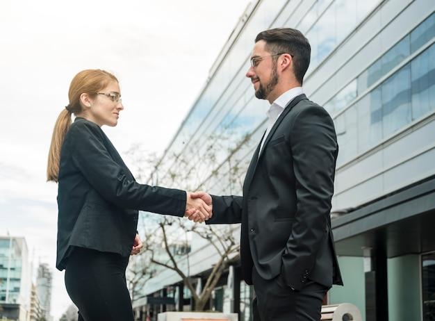 Homme d'affaires et femme d'affaires à l'extérieur de l'immeuble de bureaux se serrant la main