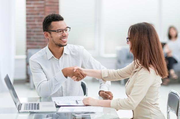 Homme d'affaires et femme d'affaires faisant un accord dans un bureau moderne
