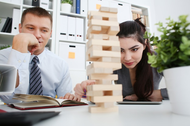 Homme d'affaires et femme d'affaires joue dans la stratégie à la main en réorganisant les blocs de bois impliqués pendant la pause au travail dans le bureau assis sur la table de jeu pile de plaisir amusant passe-temps concept.