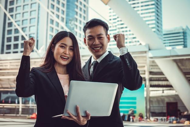 Homme d'affaires et femme d'affaires mains tiennent un ordinateur portable en plein air