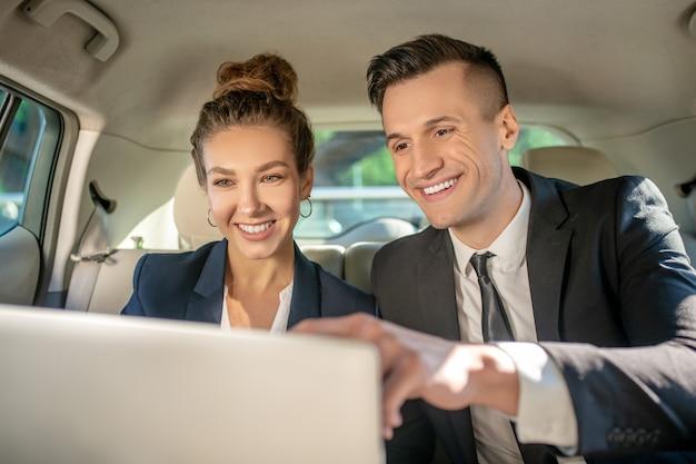 Homme affaires, et, femme affaires, à, ordinateur portable, dans, siège arrière, dans voiture