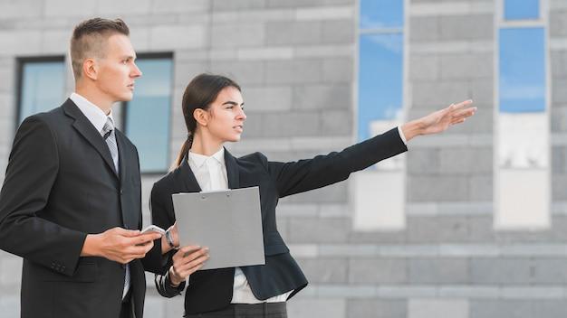 Homme d'affaires et femme d'affaires pointant quelque part
