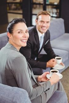 Homme d'affaires et femme d'affaires prenant le thé pendant la récréation