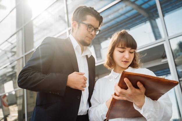Homme d'affaires et femme d'affaires regardent les papiers importants