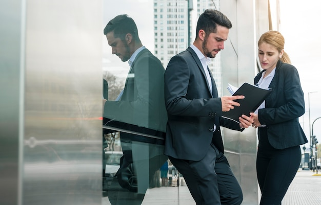 Homme affaires, femme affaires, regarder, documents, dehors, bureau