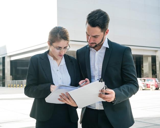 Homme d'affaires et femme d'affaires vérifiant les documents à l'extérieur