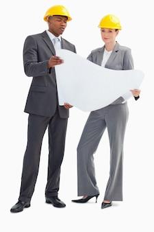 Homme d'affaires et femme avec des casques tenant du papier
