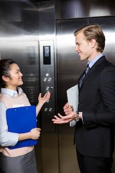 Homme d'affaires et femme debout dans un ascenseur de bureau