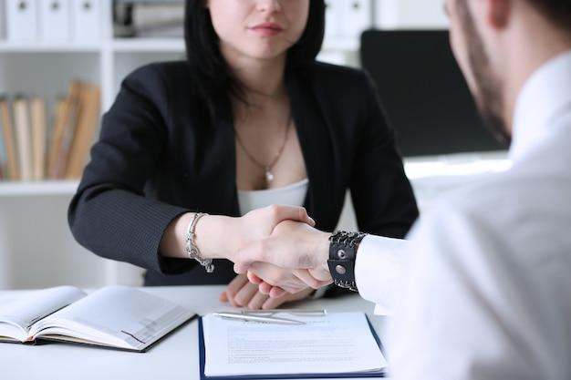 Homme d'affaires et femme se serrent la main comme bonjour en portrait de bureau.
