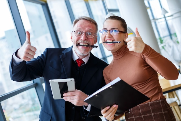 Un homme d'affaires et une femme signent un contrat et célèbrent le succès dans son bureau. tenir des stylos dans leurs dents et sourire
